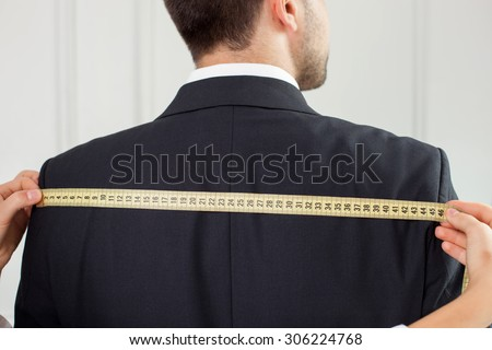 Close up of hands of skilled clothes designer. The woman is taking measurements of length of male back. She is holding a tape-measure horizontally - stock photo