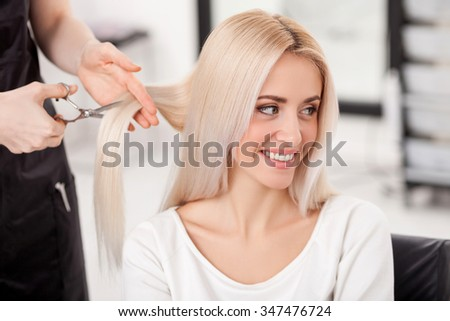 Close up of hands of skillful hairstylist cutting female hair with scissors. The blond woman is smiling and looking aside with joy. She is sitting at hairdressing salon - stock photo