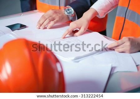 Close up of hands of two architects. The man and woman are standing near the table with sketches of construction. They are creating a plan of building - stock photo