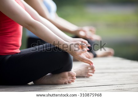 Close up of hands of two beautiful sporty fit young women meditating or breathing outdoors, Sitting in Easy (Pleasant Posture), Sukhasana, wearing sportswear working out on summer day - stock photo