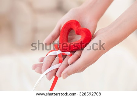 Close up of hands of women holding gift in shape of red heart. She is falling in love  - stock photo