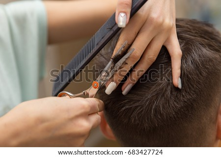 close up of hands of young barber making haircut to attractive man in barbershop.