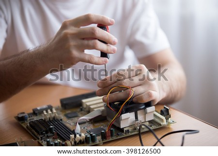 Close-up of hands of young computer engineer fixing broken pc parts at the desk in the home office - stock photo