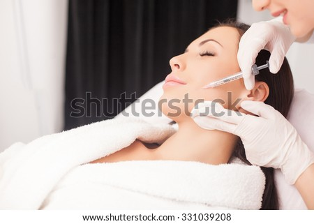 Close up of hands of young cosmetologist injecting botox in female face. She is standing and smiling. The woman is closed her eyes with relaxation - stock photo