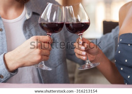 Close up of hands of young loving couple clinking glasses of red wine. They are sitting at the table in restaurant and embracing