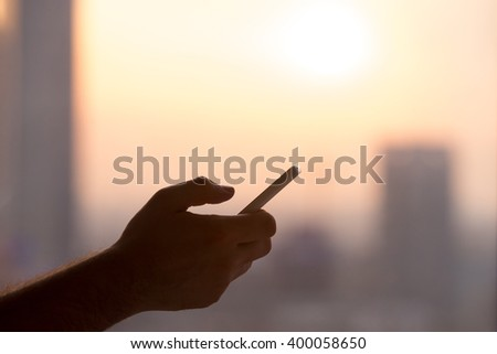 Close-up of hands of young man holding mobile phone, using smartphone app, scrolling. silhouette against sunny street view - stock photo