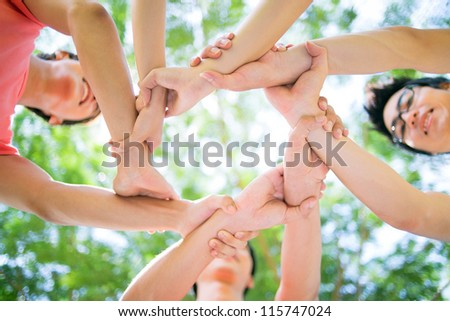 Close-up of hands of young people joined in a circle - stock photo