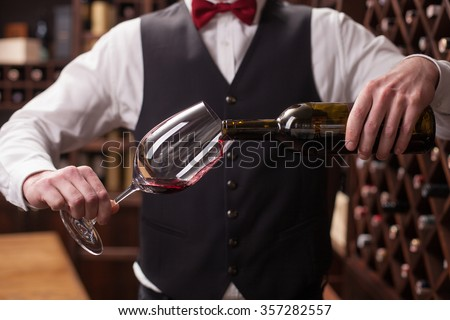 Close up of hands of young sommelier pouring red wine from bottle into glass. He is standing in a cellar