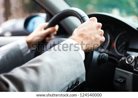 Close-up of hands on a steering wheel - stock photo