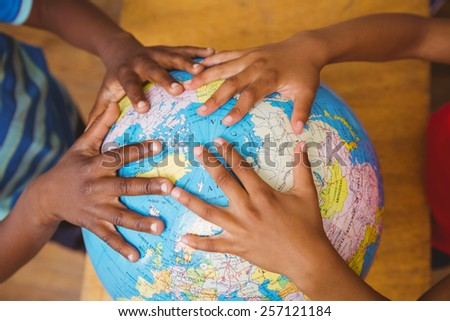 Close up of hands on globe in classroom - stock photo