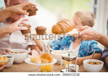 Close-up of hands passing cupcake and bread while having breakfast at home - stock photo