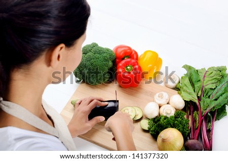 Close up of hands slicing and chopping raw vegetables as meal preparation in a kitchen - stock photo