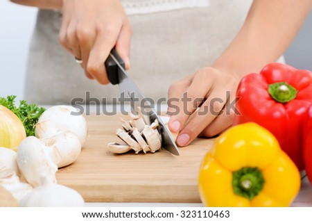 Close up of hands slicing and chopping raw vegetables as meal preparation in a kitchen