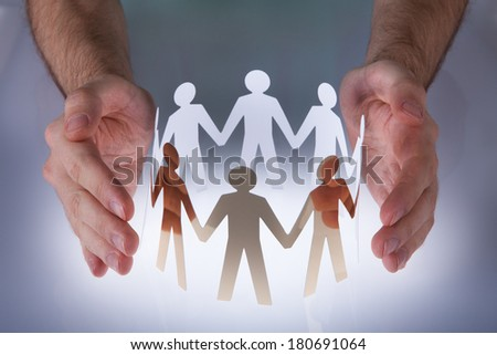 Close-up Of Hands Taking Care Of Paper People - stock photo