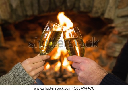 Close-up of hands toasting champagne flutes in front of lit fireplace - stock photo