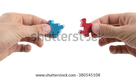 Close-up of hands trying to connect big jigsaw puzzle pieces over white background