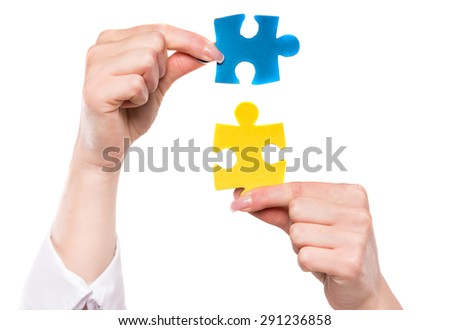 Close-up of hands trying to connect small jigsaw puzzles over white background.