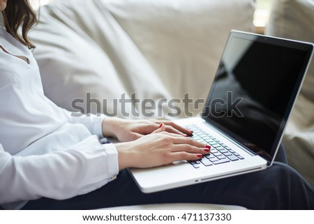 Close-up of hands typing on laptop keyboard in the home office
