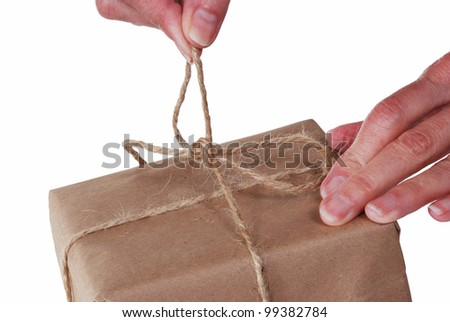 Close up of hands untying string on a package - stock photo