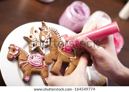 Close-up of hands with gingerbread cookie and pipping bag - stock photo