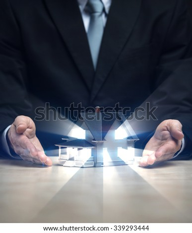 Close up of hands with house model shining. Concept of deal and real estate - stock photo