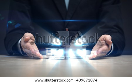 Close up of hands with house model shining. Concept of deal and realty - stock photo