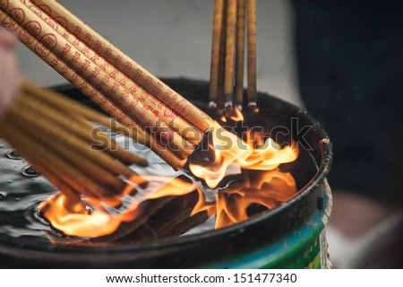 Close-up of hands with incense sticks - stock photo