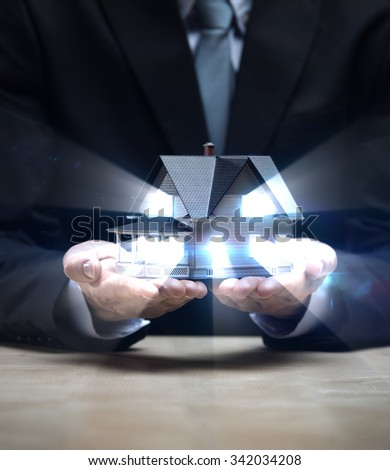 Close up of hands with little home shining. Concept of deal and real estate - stock photo
