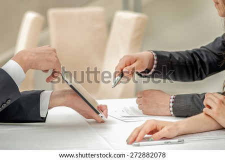 Close-up of hands with tablet and laptop. Businessmen on corporate meeting. Hands of young people at the table - stock photo