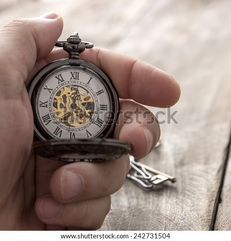 close up of hands with vintage pocket watch over wooden background  - stock photo