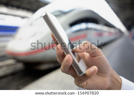 Close up of hands woman using her cell phone at a station platform, train background - stock photo