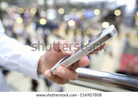 Close up of hands woman using her cell phone in train station, background people - stock photo