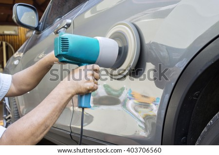 Close up of hands worker using polisher to polish a car body in the workshop