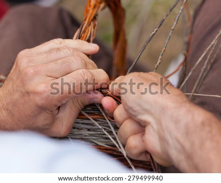 Close up of hands working in a basket costruction
