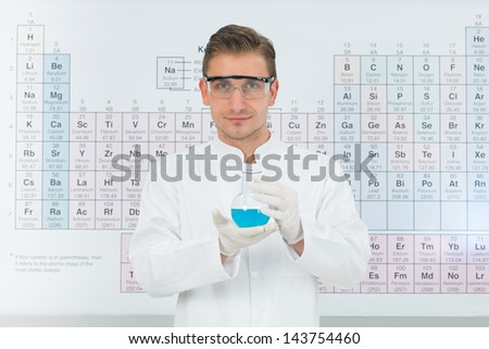 close-up of handsome male scientist smiling and holding a flask with blue substance, with periodic table in background, in a laboratory - stock photo