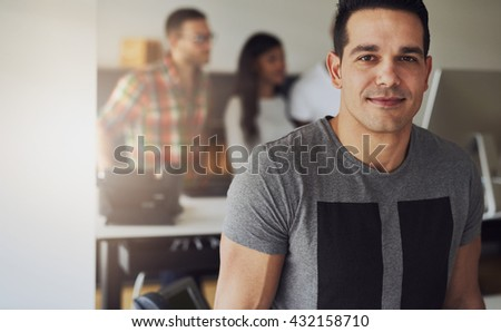Close up of handsome male worker wearing gray short sleeve shirt in small office with other employees behind him - stock photo