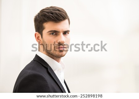 Close-up of handsome man on the light background is looking at the camera. - stock photo