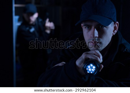 Close up of handsome police officer with torch  - stock photo
