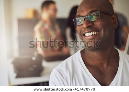 Close up of handsome smiling worker in white shirt and eyeglasses with three out of focus employees behind him in meeting - stock photo