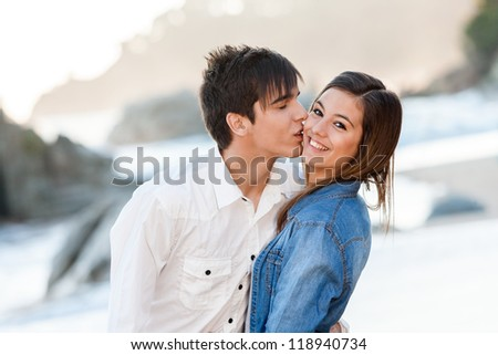 Close up of handsome teen couple in love on beach. - stock photo