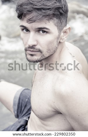 Close up of handsome young muscle man shirtless outdoors looking at camera, profile view - stock photo