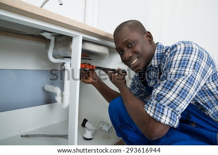 Close-up Of Happy African Male Plumber Fixing Pipe Of Sink In Kitchen - stock photo