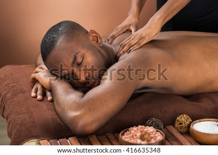 Close-up Of Happy African Man Receiving Massage Treatment - stock photo