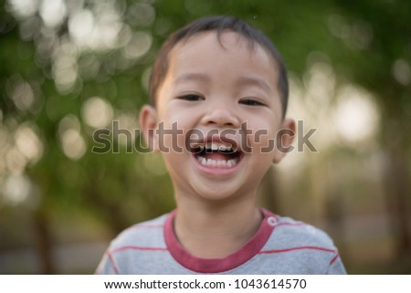 Close up of Happy asian boy smiling in the park. Little Asian child portrait photo in the park.