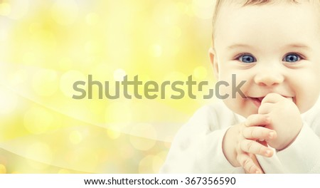 close up of happy baby over yellow background - stock photo
