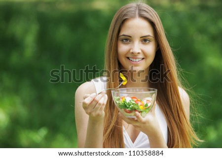 Close-up of happy beautiful young woman eating vegetable salad