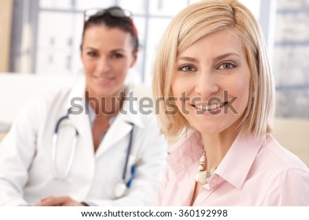 Close up of happy blonde casual caucasian female patient at doctor's medical office. Smiling and looking at camera. - stock photo