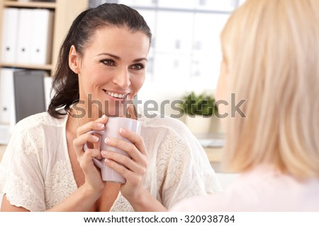 Close up of happy casual brunette receptionist with coffee cup in hand at business office, smiling. - stock photo