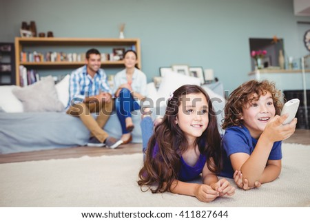 Close-up of happy children with remote while parents in background at home - stock photo