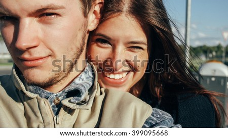 close up of happy emotional couple hugging and winking on background of urban city airport
